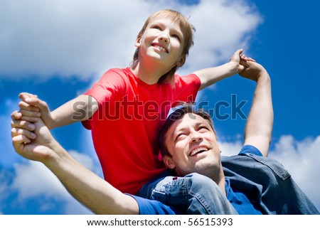 happy father with his son on a background of sky - stock photo