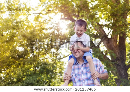 Happy father with his son spending time together outside in green nature. - stock photo