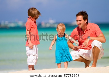 Happy father with his two kids enjoying beach vacation - stock photo