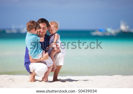 Happy father with his two kids on tropical beach vacation - stock photo