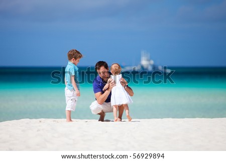Happy father with his two kids on tropical beach vacation
