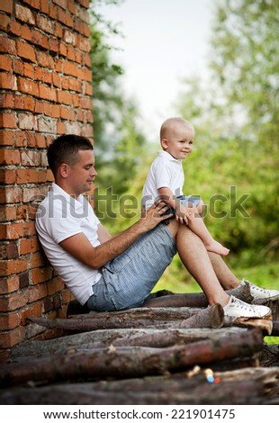 Happy father with little son spending time in nature by the old house - stock photo