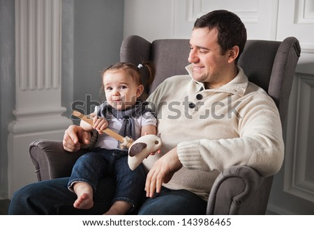 Happy father with one year old baby girl indoor - stock photo