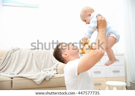 Happy father with sweet baby in the room - stock photo