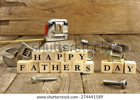 Happy Fathers Day blocks with tools on a rustic wood background - stock photo