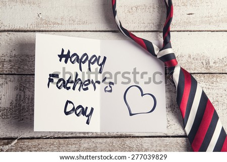 Happy fathers day sign on paper and colorful tie laid on wooden floor backround. - stock photo