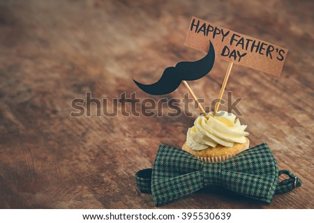 Happy fathers day special cupcake and bow tie on wooden table - stock photo