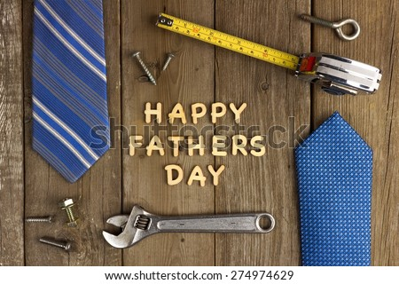 Happy Fathers Day wooden letters on a rustic wood background with tools and ties frame - stock photo