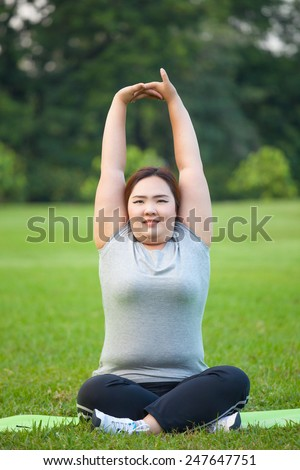 Happy fatty asian woman posing outdoor in a park - stock photo