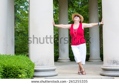 Happy Feel Good trendy modern grandma leaning with outstretched arms between two columns celebrating the sunshine and nature with her head tilted to the sun - stock photo
