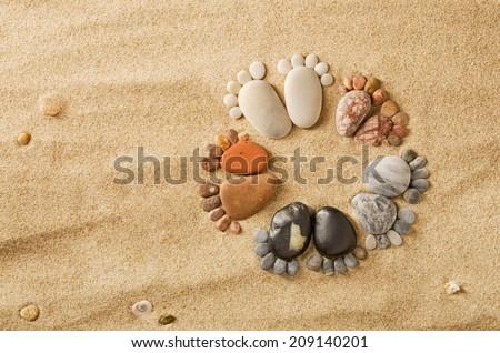 Happy feet. Stone arranged like footprints on the beach - stock photo
