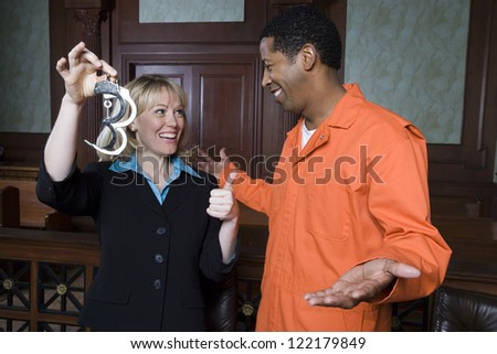Happy female advocate with prisoner released after judgment - stock photo