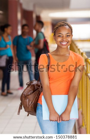 happy female African American college student holding books - stock photo