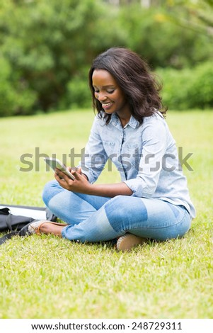 happy female african american college student using mobile phone outdoors