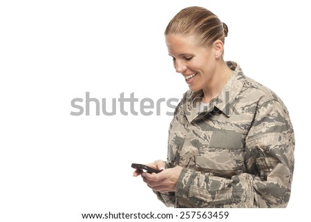 Happy female airman text messaging on mobile phone - stock photo