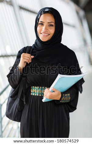 happy female arabian college student holding a book - stock photo
