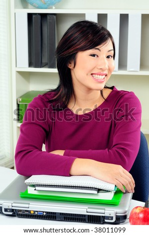 Happy Female Asian Student In Class Smiling Leaning On Her Books