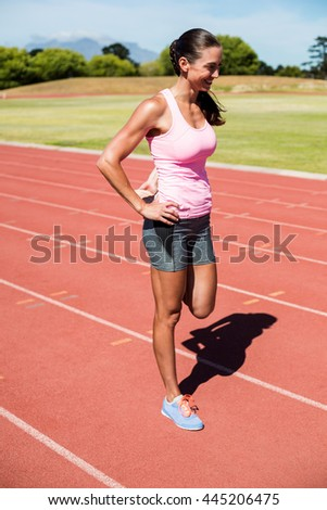 Happy female athlete warming up on the running track on a sunny day - stock photo