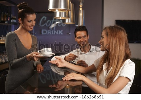 Happy female bartender serving young couple in bar. - stock photo