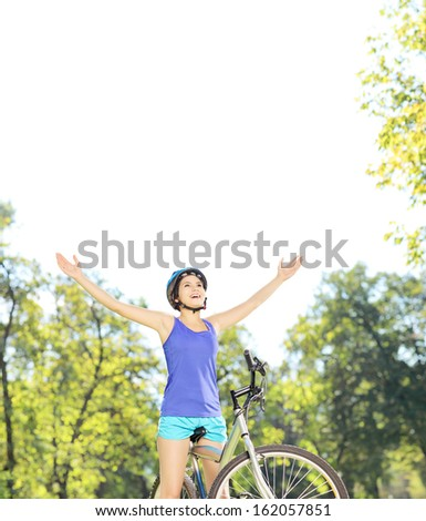 Happy female biker posing with raised hands on a mountain bike outdoors, shot with a tilt and shift - stock photo
