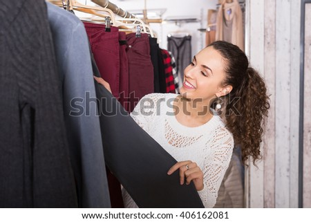 Happy female brunette choosing new trousers and smiling