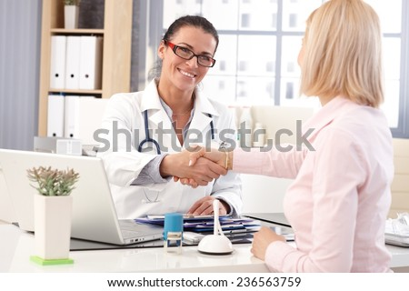 Happy female brunette doctor at medical office with patient, wearing glasses, stethoscope and lab coat. Shaking hands, smiling. - stock photo