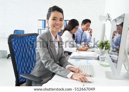 Happy female business executive working on computer