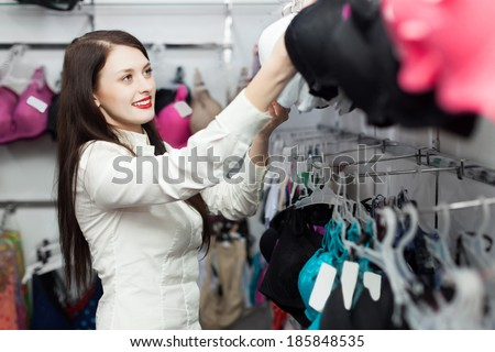 Happy female buyer choosing bra at clothing shop - stock photo