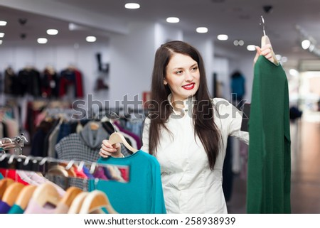 Happy female buyer with two sweaters at clothing store