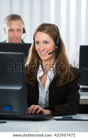 Happy Female Call Center Executive Working On Computer In Office - stock photo