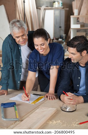 Happy female carpenter working on blueprint with male colleagues at table in workshop - stock photo