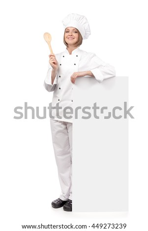 happy female chef, cook or baker holding spoon and standing next to the banner with empty copy space for you text isolated on white background. advertisement blank board. your text here - stock photo
