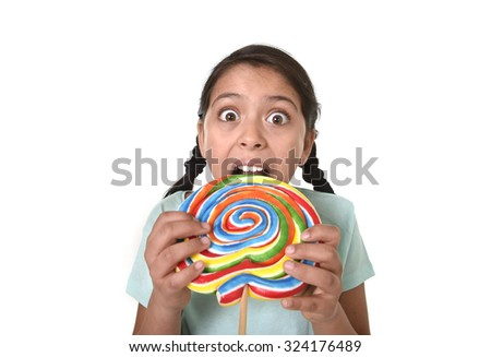 happy female child holding big lollipop candy biting the candy with her teeth in freak crazy funny face expression in sugar addiction and kid love for sweet concept isolated on white background - stock photo