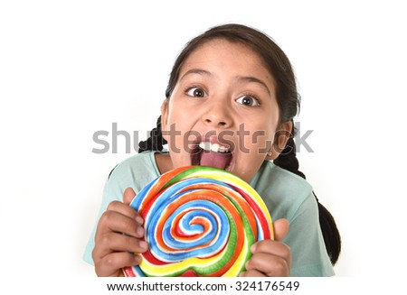 happy female child holding big lollipop candy licking the candy with her tongue in cheerful face expression in sugar addiction and kid love for sweet concept isolated on white background - stock photo