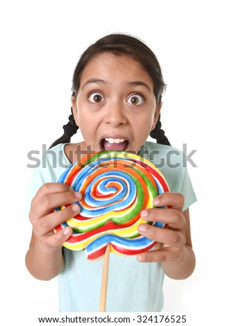 happy female child holding big lollipop candy licking the candy with her tongue in freak crazy funny face expression in sugar addiction and kid love for sweet concept isolated on white background - stock photo