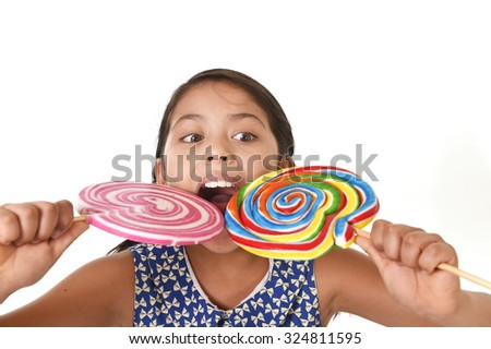 happy female child wearing dress eating two huge lollipop at once having fun in sugar addiction and kid love for sweet candy concept isolated on white background - stock photo