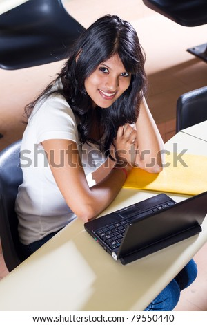 happy female college student in classroom - stock photo
