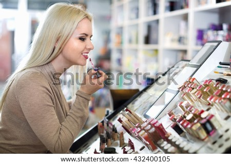 Happy female customer buying red lipstick in makeup section - stock photo