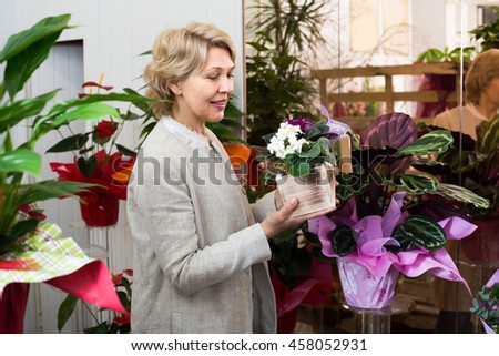 Happy female customer choosing flowers in floral department