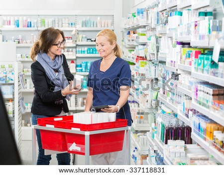 Happy female customer showing product to chemist in pharmacy - stock photo