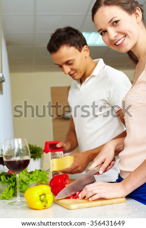 Happy female cutting vegetables for salad in the kitchen