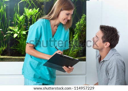 Happy female dentist with clipboard looking at male patient in clinic - stock photo