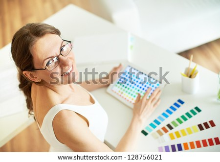 Happy female designer looking at camera at workplace - stock photo