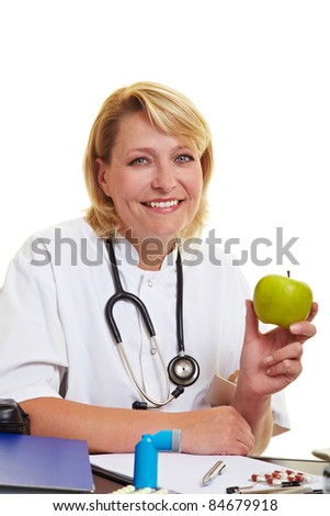 Happy female doctor at desk holding a green apple - stock photo