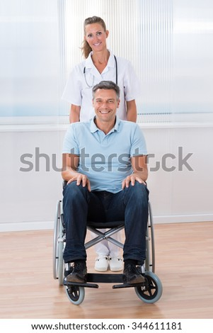Happy Female Doctor Carrying Male Patient On Wheelchair - stock photo