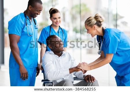happy female doctor greeting disabled patient in hospital - stock photo