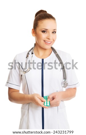 Happy female doctor holding pills. - stock photo