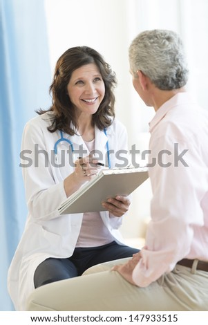 Happy female doctor with clipboard looking at patient in clinic - stock photo