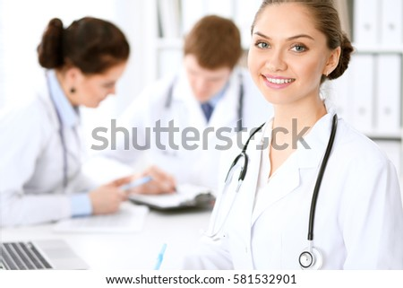 Happy female doctor with medical staff while sitting at the table.  Successful team at health care and medicine concept