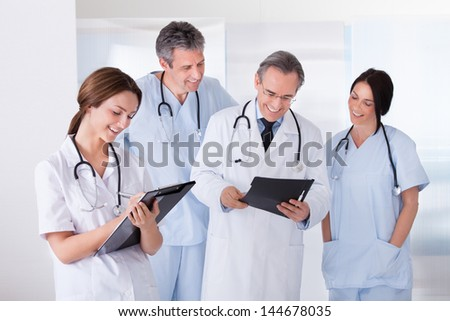 Happy Female Doctor With Stethoscope And Clipboard With Her Colleague - stock photo